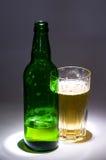 De groene fles van het bier met glas Stock Foto's