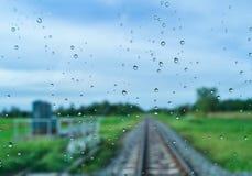 De groene gebieden en de spoorwegsporen na regen achter het venster, kijken vers, ontspannen, kalmeren en stil Stock Fotografie