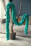 De groene gebreide sjaal van merinoswol hangt op een kunstmatige boom i Stock Afbeelding