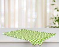 De groene geruite keukenhanddoek op lijst defocused over gordijnachtergrond Royalty-vrije Stock Afbeeldingen