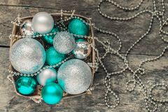 de groene Kerstmisballen en zilveren, parels liggen in een houten mand t Stock Foto