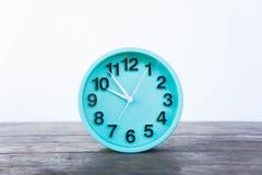 De Groene klok op een houten lijst aangaande een witte achtergrond Royalty-vrije Stock Afbeeldingen