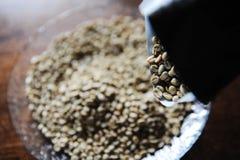 De groene koffiebonen gieten van pakket aan plaat stock fotografie