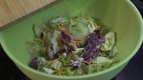 In de groene kom met salade voeg rode kool toe stock videobeelden
