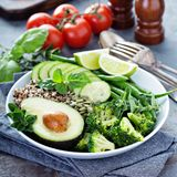 De groene kom van de veganistlunch met quinoa en avocado stock afbeeldingen