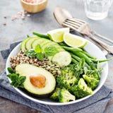 De groene kom van de veganistlunch met quinoa en avocado stock foto's