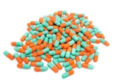 De groene oranje capsule van kleurenpillen op witte achtergrond Stock Foto's