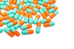 De groene oranje capsule van kleurenpillen op witte achtergrond Stock Foto