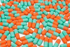 De groene oranje capsule van kleurenpillen op witte achtergrond Royalty-vrije Stock Afbeeldingen