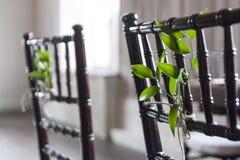 De groene ruskusbladeren die met streng worden gebonden verfraaien de houten stoel stock afbeeldingen