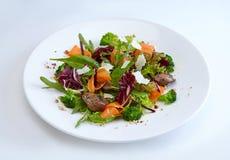 De groene salade met chiken op witte plaat stock afbeelding