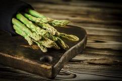 De groene sappige asperge ligt op een houten raad op een bruine houten lijst royalty-vrije stock foto