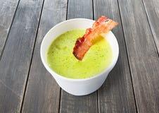 De groene soep van de de lenteerwt met bacon bij grijs hout stock afbeeldingen