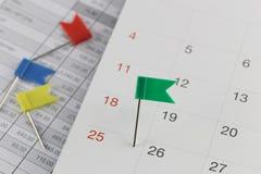 De groene Spelden aan Wilde stakingen op de kalender naast het aantal van twen Royalty-vrije Stock Afbeelding