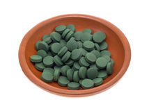 De groene tabletten van het ijzersupplement in een kleine kom Stock Foto