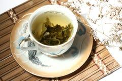 De groene thee in een kop met een thee doorbladert Royalty-vrije Stock Foto