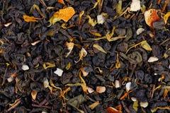 De groene thee van Ceylon met droge bloemen en geglaceerde oranje achtergrond stock afbeelding