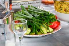 De groene uien, de komkommers en de tomaten op een schotel sluiten omhoog stock afbeeldingen