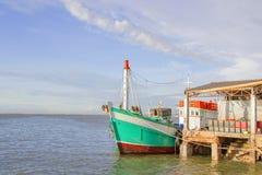 De groene vissersboot wordt vergoelijkt tegen de pijler met blauw Stock Foto
