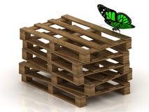 De groene vlinder zit op een stapel houten pallets Royalty-vrije Stock Afbeelding
