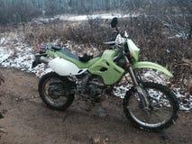 De groene vuilfiets in modder en sneeuw behandelde slepen Stock Afbeeldingen