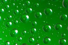 De groene waterdruppeltjes op een glas sluiten omhoog macroschot Regenachtige dagen royalty-vrije stock foto's