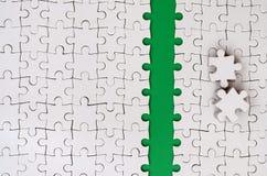 De groene weg wordt gelegd op het platform van een witte gevouwen puzzel De ontbrekende elementen van het raadsel worden dichtbij Royalty-vrije Stock Foto's