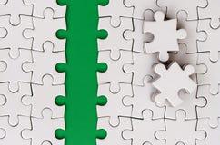 De groene weg wordt gelegd op het platform van een witte gevouwen puzzel De ontbrekende elementen van het raadsel worden dichtbij Royalty-vrije Stock Afbeeldingen