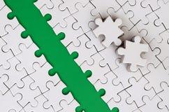 De groene weg wordt gelegd op het platform van een witte gevouwen puzzel De ontbrekende elementen van het raadsel worden dichtbij Stock Afbeelding