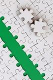 De groene weg wordt gelegd op het platform van een witte gevouwen puzzel De ontbrekende elementen van het raadsel worden dichtbij Stock Foto's