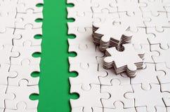 De groene weg wordt gelegd op het platform van een witte gevouwen puzzel De ontbrekende elementen van het raadsel worden dichtbij Royalty-vrije Stock Fotografie