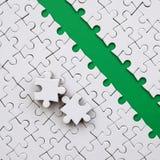 De groene weg wordt gelegd op het platform van een witte gevouwen puzzel De ontbrekende elementen van het raadsel worden dichtbij Stock Foto