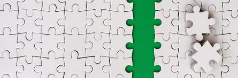 De groene weg wordt gelegd op het platform van een witte gevouwen puzzel De ontbrekende elementen van het raadsel worden dichtbij Stock Fotografie