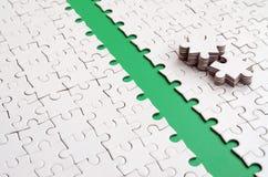 De groene weg wordt gelegd op het platform van een witte gevouwen puzzel De ontbrekende elementen van het raadsel worden dichtbij Stock Afbeeldingen