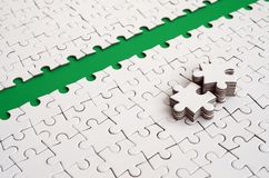 De groene weg wordt gelegd op het platform van een witte gevouwen puzzel De ontbrekende elementen van het raadsel worden dichtbij Royalty-vrije Stock Afbeelding