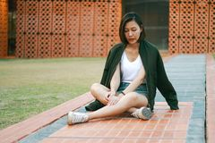De groene zitting van de overhemdsvrouw op het gazon royalty-vrije stock fotografie