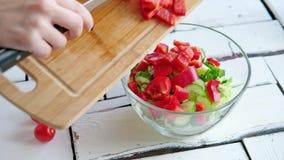 De groenten liggen op een lijst aangaande een hakbord stock videobeelden