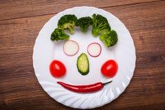 De groenten op de plaat in de vorm van een glimlach op een houten oppervlakte De mening vanaf de bovenkant Royalty-vrije Stock Foto