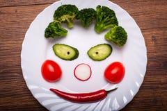 De groenten op de plaat in de vorm van een glimlach op een houten oppervlakte De mening vanaf de bovenkant Royalty-vrije Stock Fotografie
