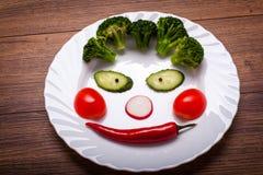 De groenten op de plaat in de vorm van een glimlach op een houten oppervlakte De mening vanaf de bovenkant Stock Afbeeldingen