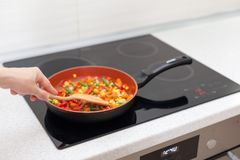 De groenten zijn in een pan Vrouw die kleurrijke verse groenten op een elektrisch fornuis koken stock foto's