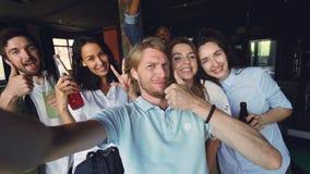 De groep collega's neemt samen selfie, houdt de jonge mens camera en stellend, houden zijn medewerkers dranken stock videobeelden