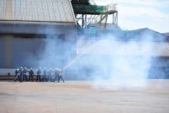 de groep de brandbestrijdersmens is inspuit nevel het water aan brandacc Stock Afbeeldingen