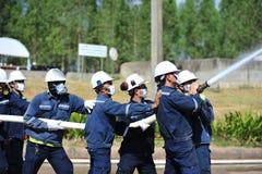 de groep de brandbestrijdersmens is inspuit nevel het water aan brandacc Royalty-vrije Stock Foto