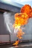 de groep de brandbestrijdersmens is inspuit nevel het water aan brandacc Stock Fotografie