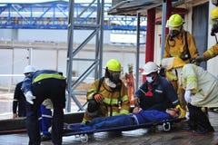 de groep de brandbestrijdersmens is inspuit nevel het water aan brandacc Royalty-vrije Stock Foto's