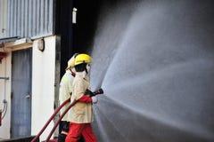 de groep de brandbestrijdersmens is inspuit nevel het water aan brandacc Stock Foto