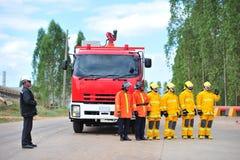 de groep de brandbestrijdersmens is inspuit nevel het water aan brandacc Royalty-vrije Stock Afbeeldingen