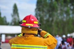 de groep de brandbestrijdersmens is inspuit nevel het water aan brandacc Stock Foto's