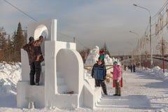De groep deelnemers doet een beeldhouwwerk van sneeuw Royalty-vrije Stock Afbeeldingen